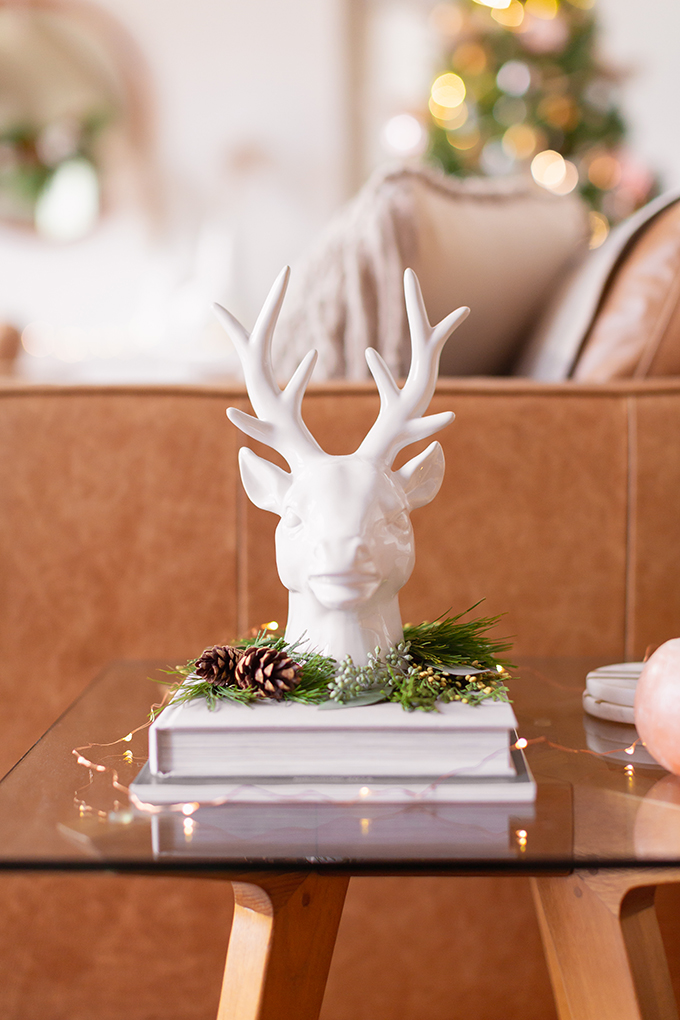 Apartment Friendly Modern Holiday Decor | White Reindeer Head Sculpture with with added greenery and fairy lights | Bohemian, Mid Century Modern Holiday Decor | Bohemian Holiday Home Tour 2018 | Caramel Mid Century Modern Leather Couches | Canadian Tire CANVAS Ornaments // JustineCelina.com