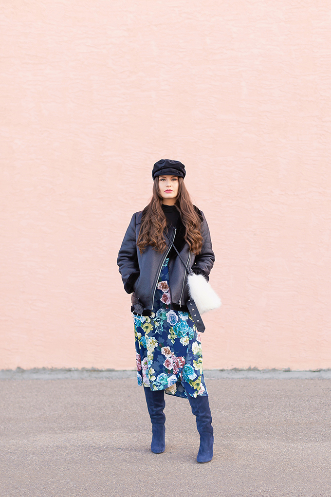 Winter 2019 Lookbook | Edgy Florals: How to Style Midi Skirts for Winter | 3rd Floor Studio Angie Skirt paired with Blue Maroco Women's Over-the-knee suede boots, a black turtleneck and a longline, lined biker jacket with a black velvet baker boy hat and a white faux fur bag | How to Style a Biker Jacket for Winter // JustineCelina.com