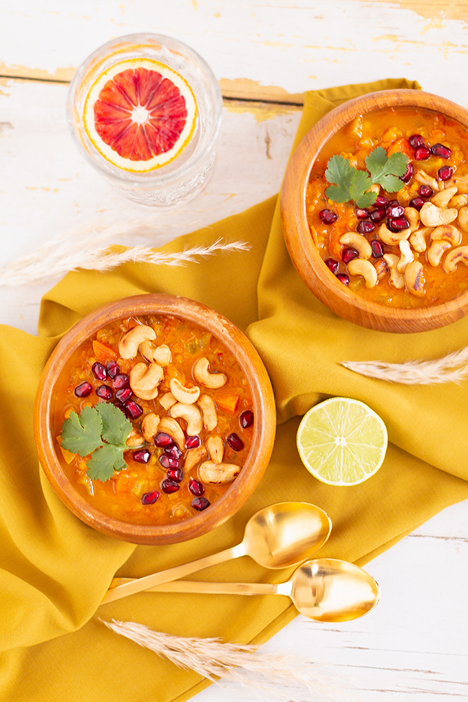 Slow Cooker Vegan Mulligatawny Soup with Red Lentils | #vegan #glutenfree | A warm bowl of vegan mulligatawny soup garnished with roasted cashews, pomegranate arils and cilantro with gold spoons and citrus water | The best vegan mulligatawny soup slow cooker recipe | vegetarian mulligatawny soup | vegetarian mulligatawny soup recipe lentils | vegetarian mulligatawny soup slow cooker | mulligatawny soup crock pot | best winter vegan slow cooker recipes // JustineCelina.com