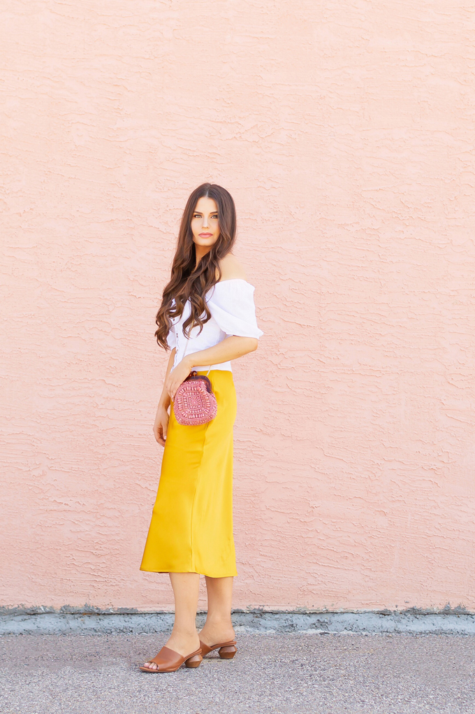 LATE SUMMER 2019 LOOKBOOK | Walking on Sunshinet: How to Style TopShop's Bias Cut Satin Midi Skirt for Summer / Autumn | TopShop Yellow Satin Skirt Outfit Ideas | Casual Daytime Transitionl Outfit Ideas | Brunette woman wearing a Topshop Yellow Satin Midi Skirt styled with a white button-down Bardot top, brown leather mules with a wooden heel and a Pantone Living Coral beaded bag | Summer 2019 Trends | Calgary Fashion & Creative Lifestyle Blogger // JustineCelina.com