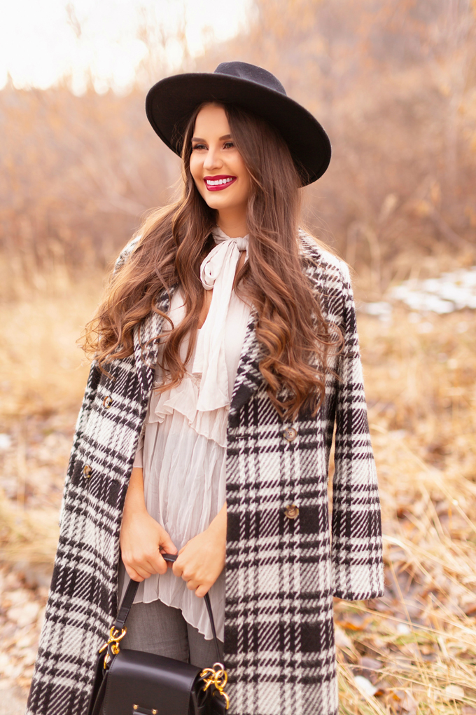 Autumn / Winter 2019 Lookbook: Checked Cowgirl | Top Fall / Winter 2019 / 2020 Trends | Top Winter 2019 Trends and How to Wear Them | Smiling Brunette woman wearing a Vero Moda Wool Plaid Coat, Ruffled, Tie Neck Blouse, Bite Beauty's Amuse Bouche Lipstick in Beetroot and a black wide brimmed black hat | Bohemian Canadian Winter Outfit Ideas | Western Winter Outfit Ideas | How to Style a Plaid Coat | Top Calgary Fashion Blogger // JustineCelina.com