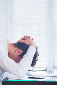 Tired man with arms over his head exhausted at his computer facing burnout