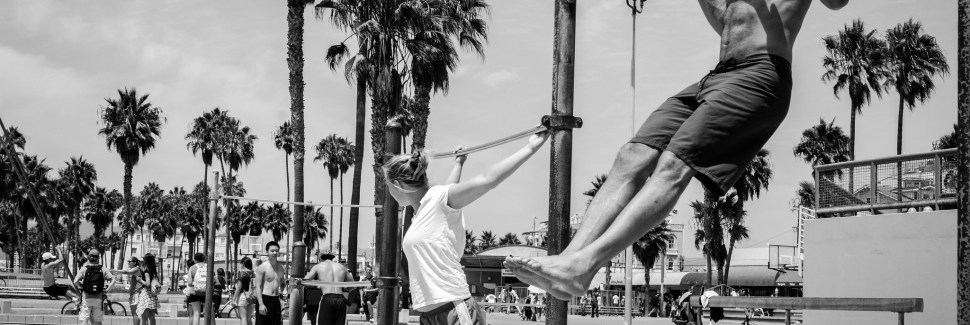 A man on the beach doing a pull up with a woman near by stretching