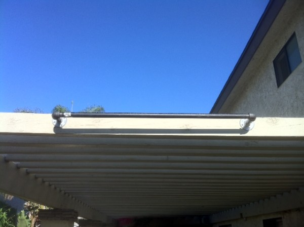 A steel pipe used as a pull up bar attached to the overhang of a patio.