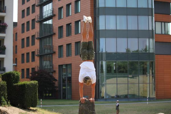 Man doing handstand in front of building