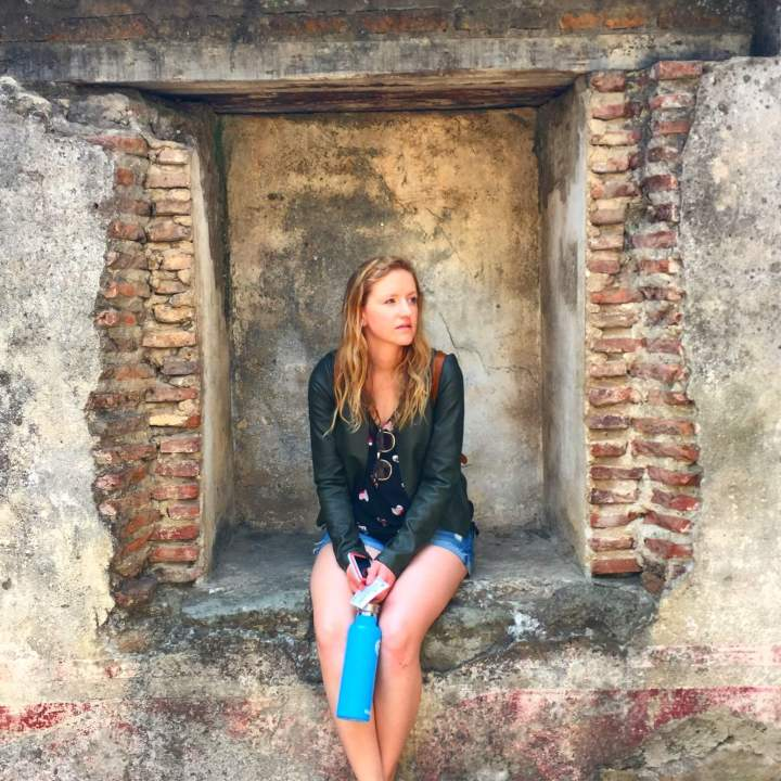 blonde woman sitting on ancient wall