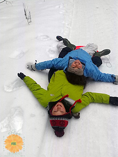 Image of two children sledding in the snow