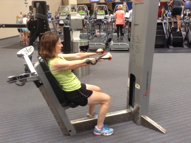 Image of woman sitting down doing a chest press