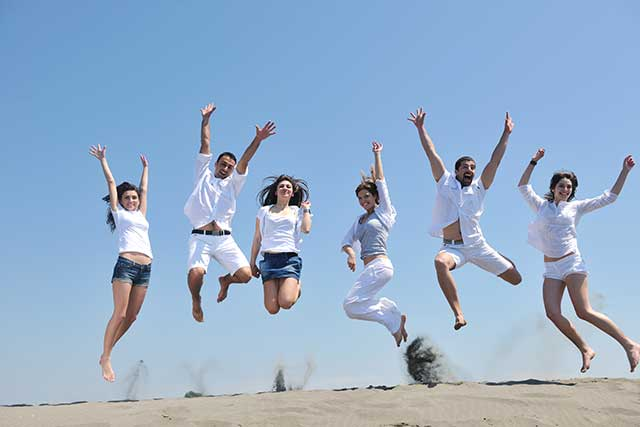 Image of a group of people jumping in the air on a beach
