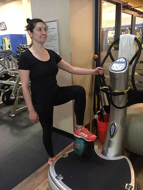 Image of woman standing with right foot resting on a medicine ball