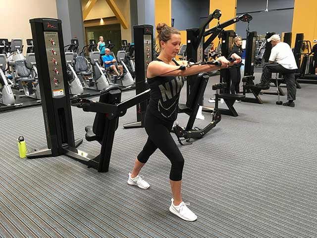 Image of women using cable machin3 for a chest press lunge