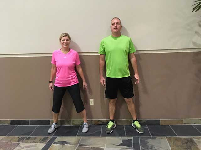 Image of 2 people using a wall as a guide to walk sideways to relieve sciatic pain