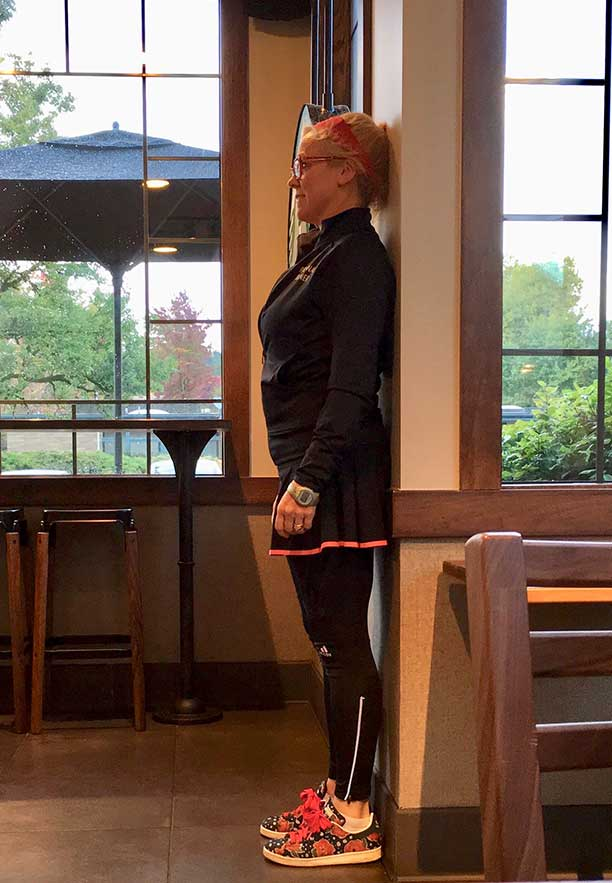 image of trainer Laura Coleman standing with her back to the wall to demonstrate how to relieve text neck