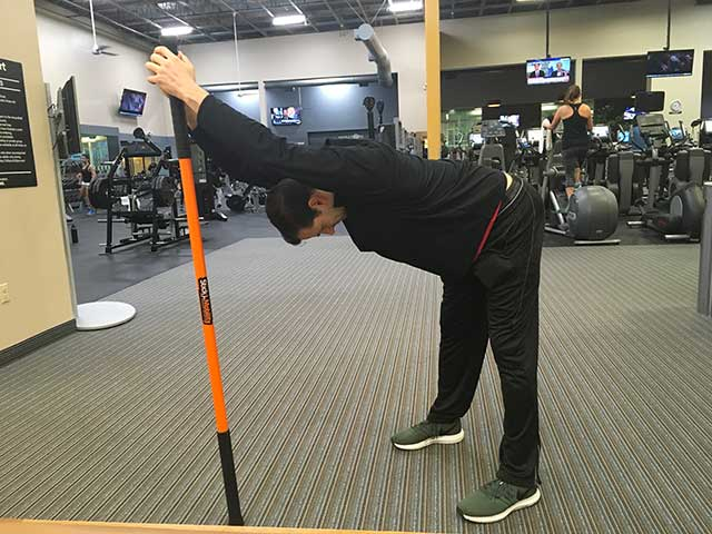 Image of man demonstrating bow exercise using a moving stick in a gym