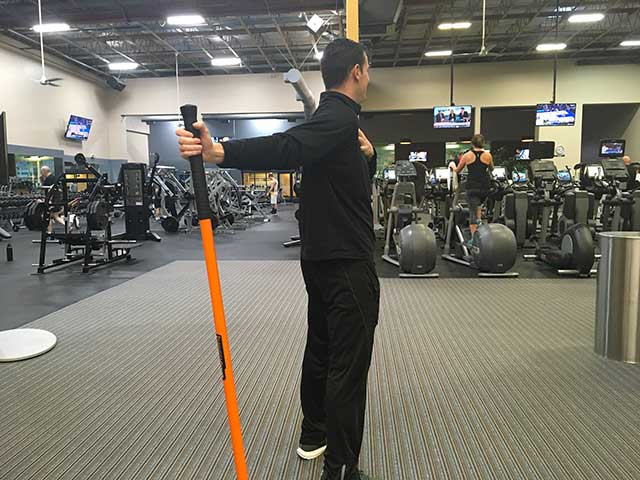 Image of man demonstrating shoulder opening exercise using a moving stick in a gym