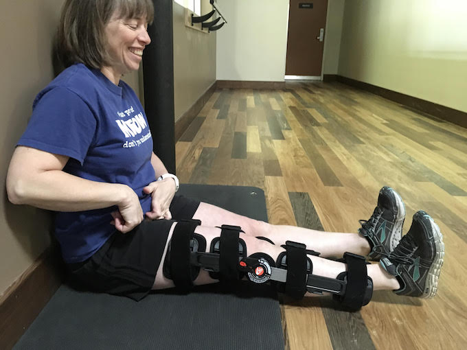 image of woman sitting against a wall with knee brace on