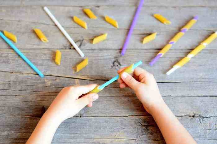 Preschoolers can improve hand eye coordination and dexterity by sliding ziti noodles onto plastic straws.