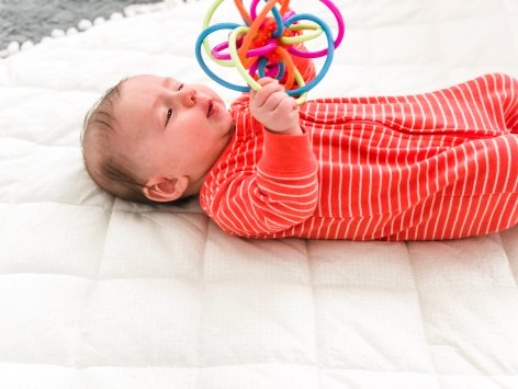 Babies learn so much about the world around them through play. Toys to explore with their hands and mouth will help develop fine motor skills for your baby. Here are some tips and activities on ways to play with your baby and help to improve the use of their hands. You can do use these play activities for your 3-6 month old baby.