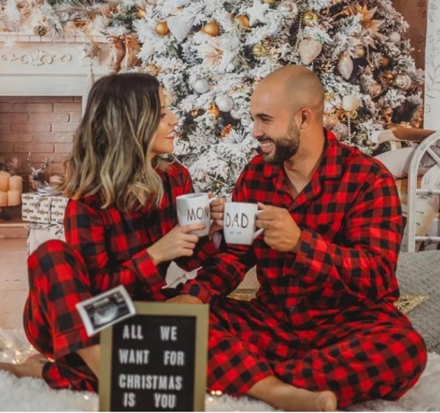 christmas pregnancy announcement with pajamas in front of the tree