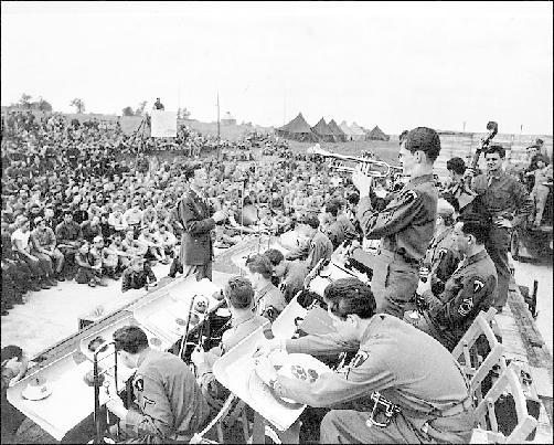 Glenn Miller conducts at an open air concert