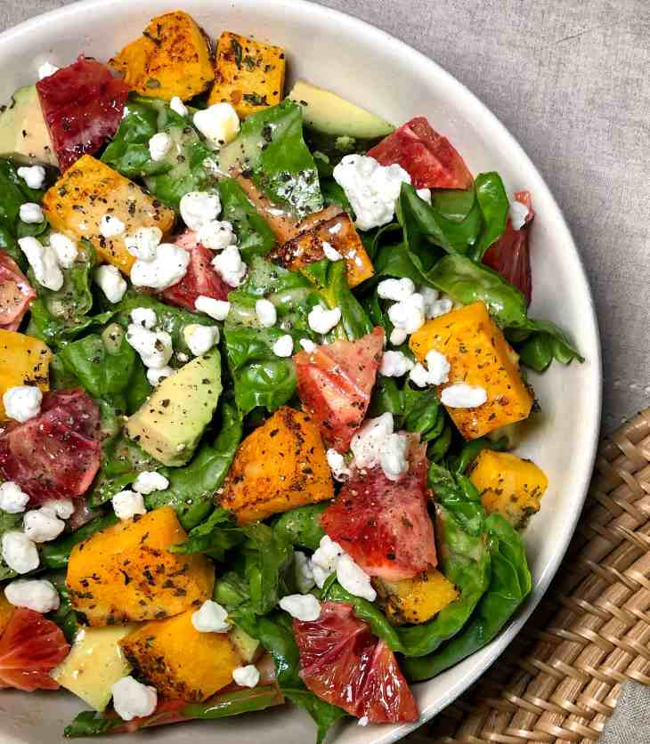 Salad with roasted squash and blood orange in a white bowl