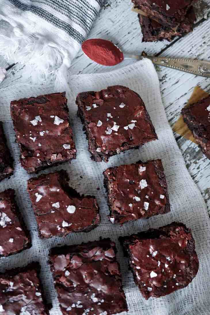 Overhead shot of brownies with a spoon of beetroot powder