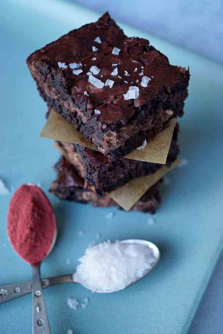 Three brownies stacked with two spoons of beetroot powder and flaky salt
