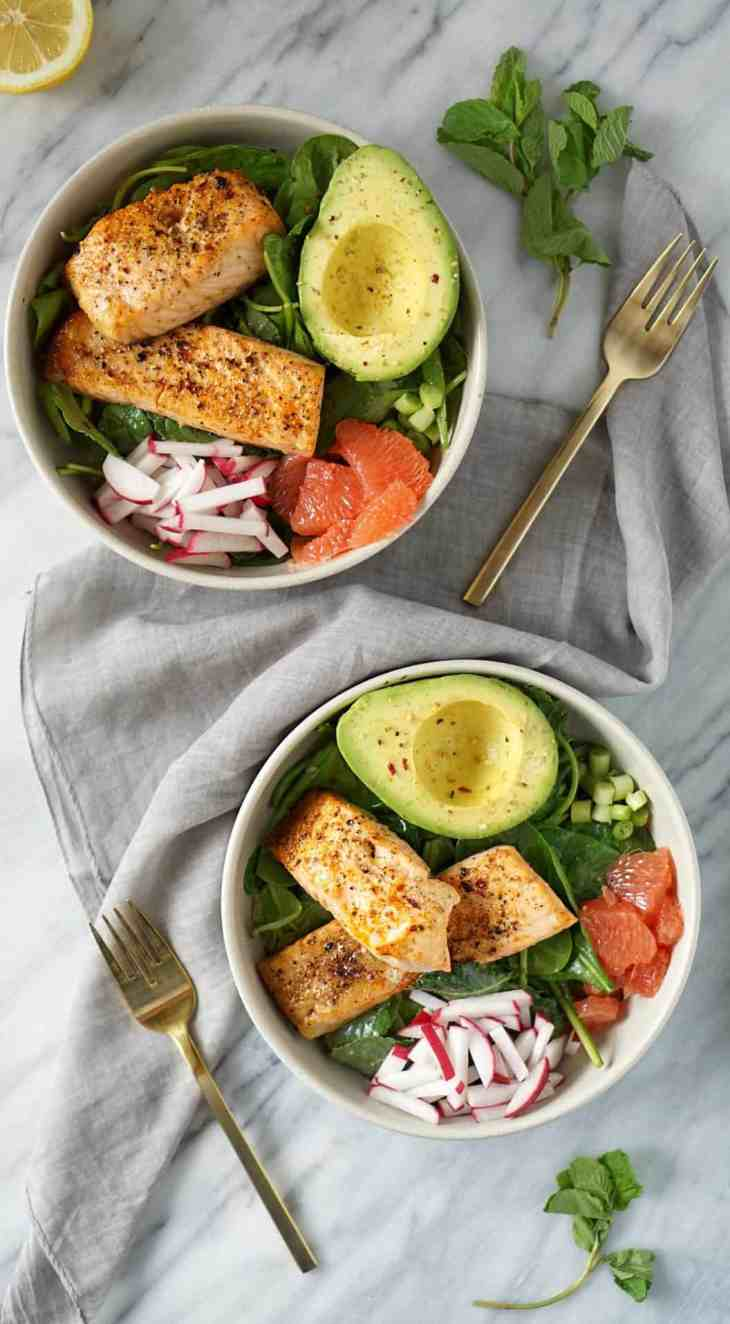 two salmon bowls with a grey napkin and gold fork