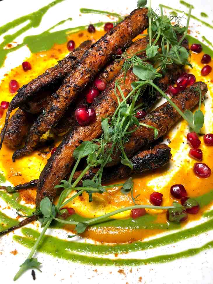 Charred carrots on a plate with sauce