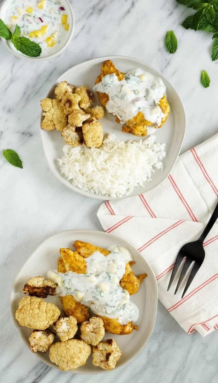 two plates of tandoori chicken with cauliflower and rice