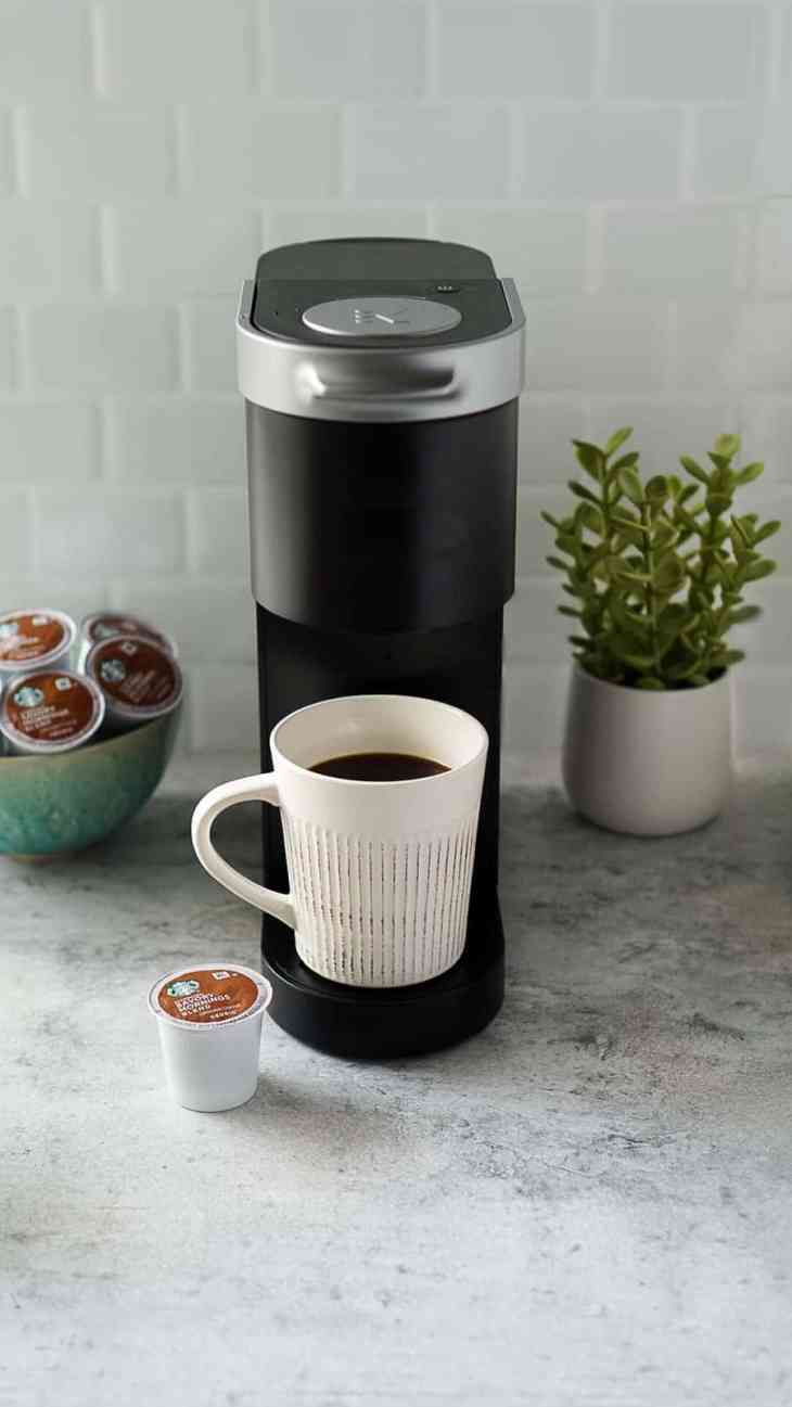 white coffee mug with k-cup pods and a black keurig