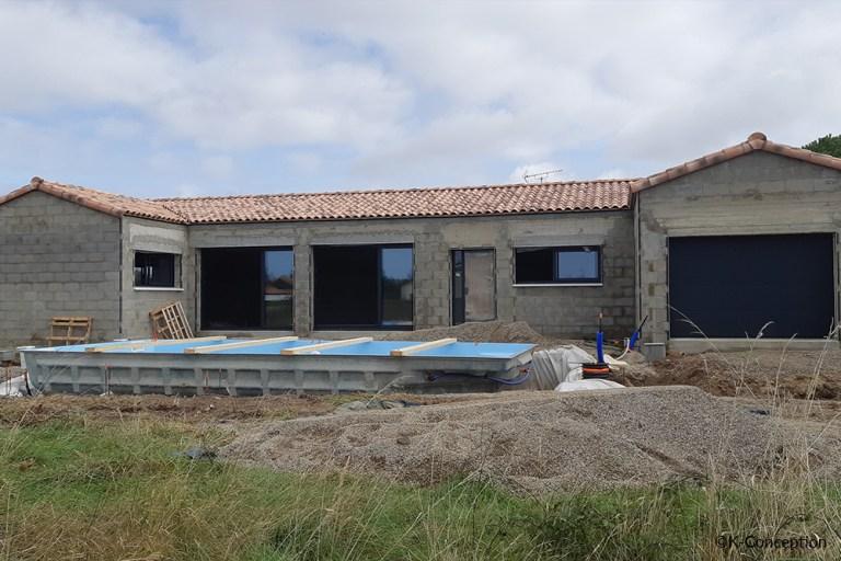 Photo d'un chantier de construction de maison individuelle à Olonne-sur-Mer. Chantier en cours. Façade avec deux grandes baies vitrée, porte d'entrée, porte de garage et piscine.