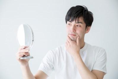 鏡を手にもって口元の髭を気にする男性