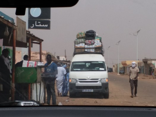 K in Motion Travel Blog. Roadside Goat and Overloaded Bus on the Way From Atar to Nouakchott, Mauritania