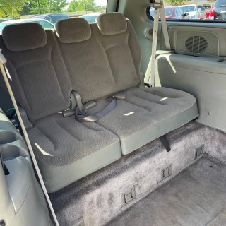 backseat of inside red van with gray cloth material and gray floorboards
