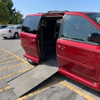 side of red van opened to show ramp coming out of van floor