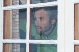Helge Kaasin titter håpefullt ut av vinduet.