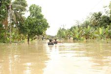 Warga mencoba melewati genangan banjir.