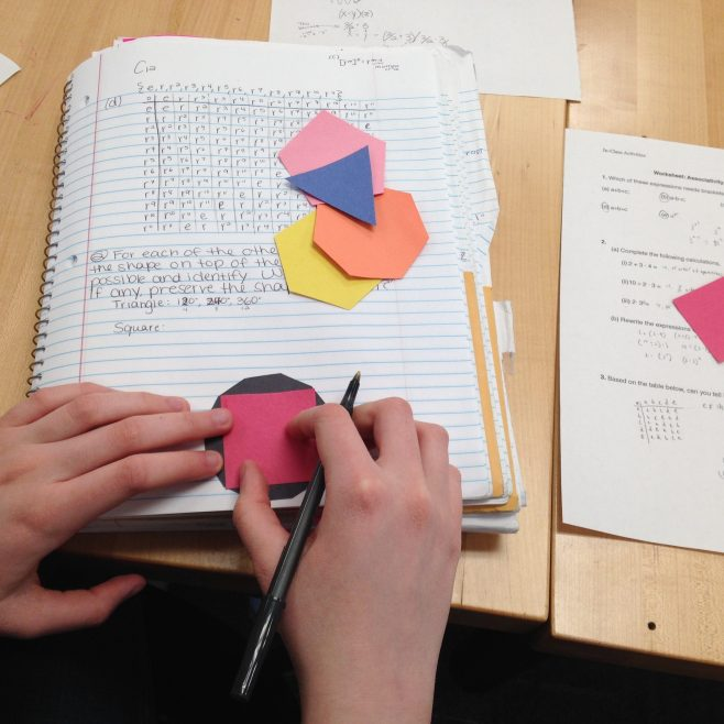 Hands of a student playing with cut outs of regular polygons.