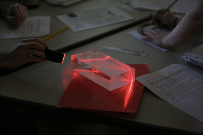 Students sent red LED light through acrylic blocks and investigated its reflection and refraction angles.