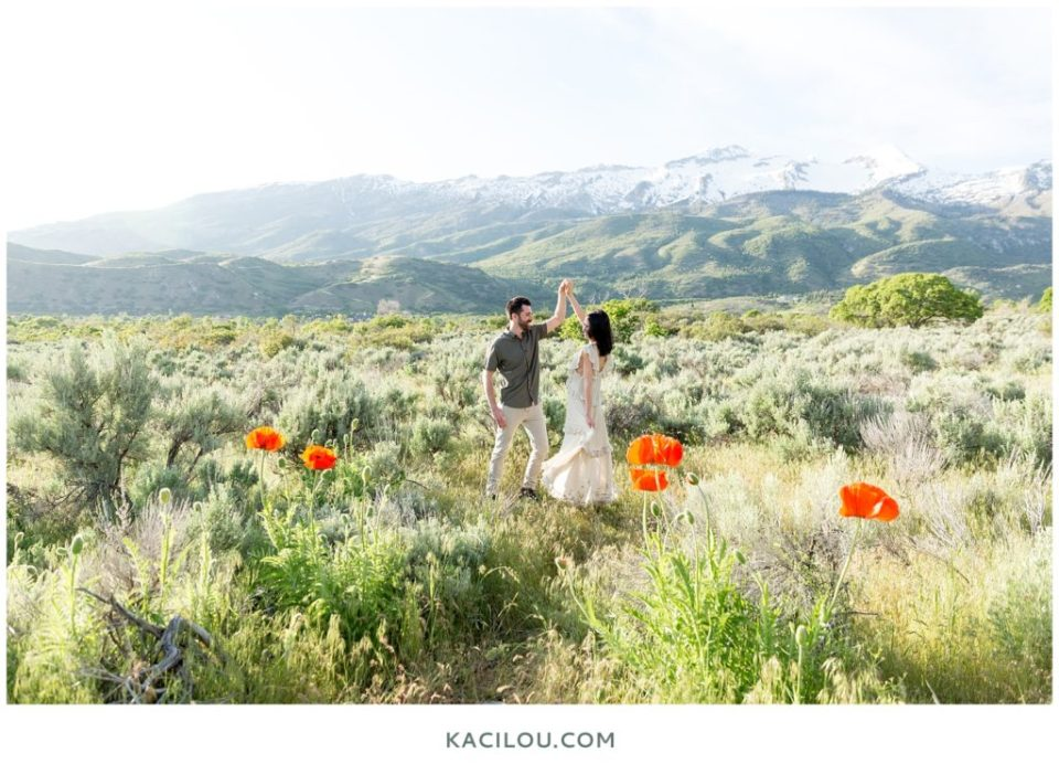 Couple dancing in field with mountains behind them in Apline poppy field Utah
