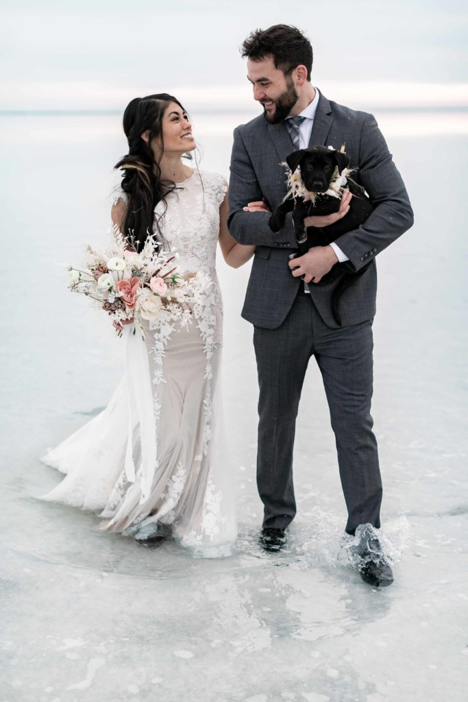 Bonneville Utah Salt Flats wedding photo of couple with their puppy when the flats are flooded.