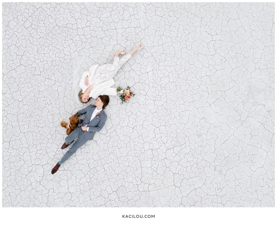 bride and groom lying on ground with dog at salt flats