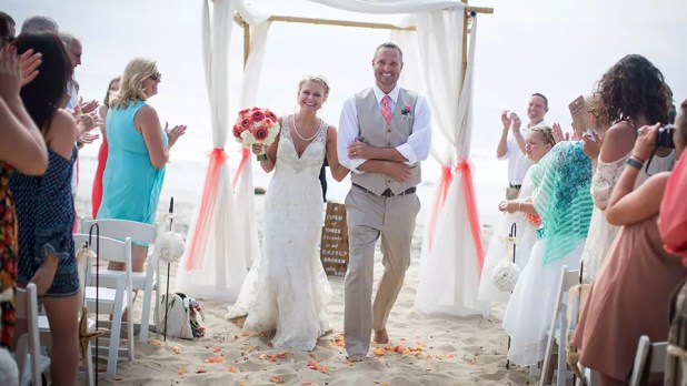 Newly-Married-Couple-Walking-Down-The-Aisle-After-Their-Beach-Wedding-Ceremony