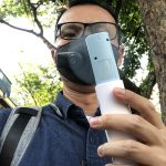 ภาพของผู้ชายใส่แว่น สวมหน้ากากันฝุ่น PM2.5 และกำลังใช้พัดลมพกพาอยู่