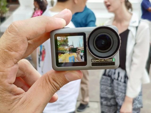 มือกำลังถือกล้อง DJI Osmo Action โดยหันเอาด้านหน้าเข้าหาตัว แล้วถ่ายภาพ