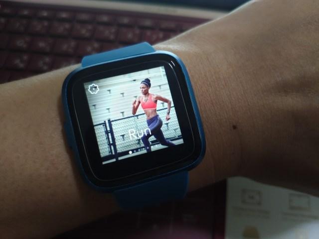 หน้าปัดนาฬิกาของ Fitbit Versa Lite Edition แสดงตัวเลือกการตรวจจับการวิ่ง เป็นภาพของผู้หญิงผิวสีน้ำตาลกำลังวิ่งอยู่
