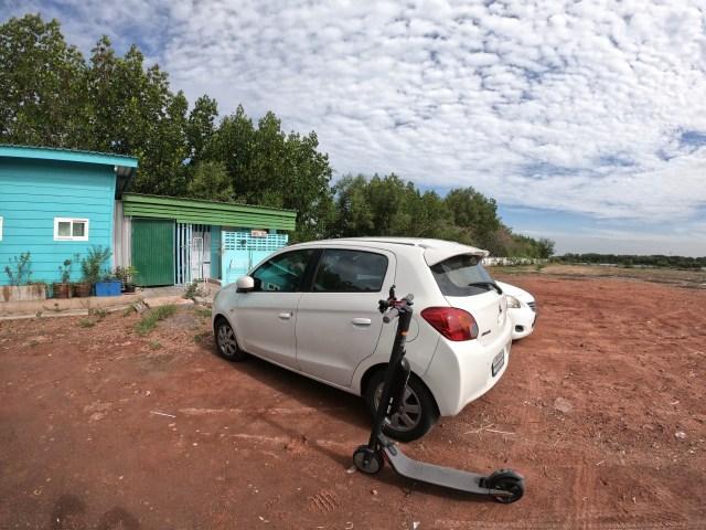 สกู๊ตเตอร์ไฟฟ้า จอดอยู่ใกล้ๆ กับรถยนต์สีขาว ที่ลานกว้างๆ