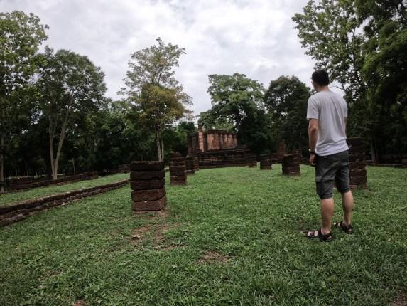 ผู้ชายใส่เสื้อยืดสีขาว กางเกงขาสั้น กำลังยืนหันหลังให้อยู่ทางขวามือ กำลังมองไปที่ซากโบราณสถานในอุทยานประวัติศาสตร์กำแพงเพชร