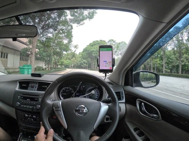 ภาพภายในห้องโดยสารรถยนต์ มีสมาร์ทโฟนทำหน้าที่เป็นอุปกรณ์นำทาง